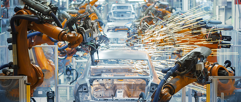 Robotic arms in automative manufacturing facility.