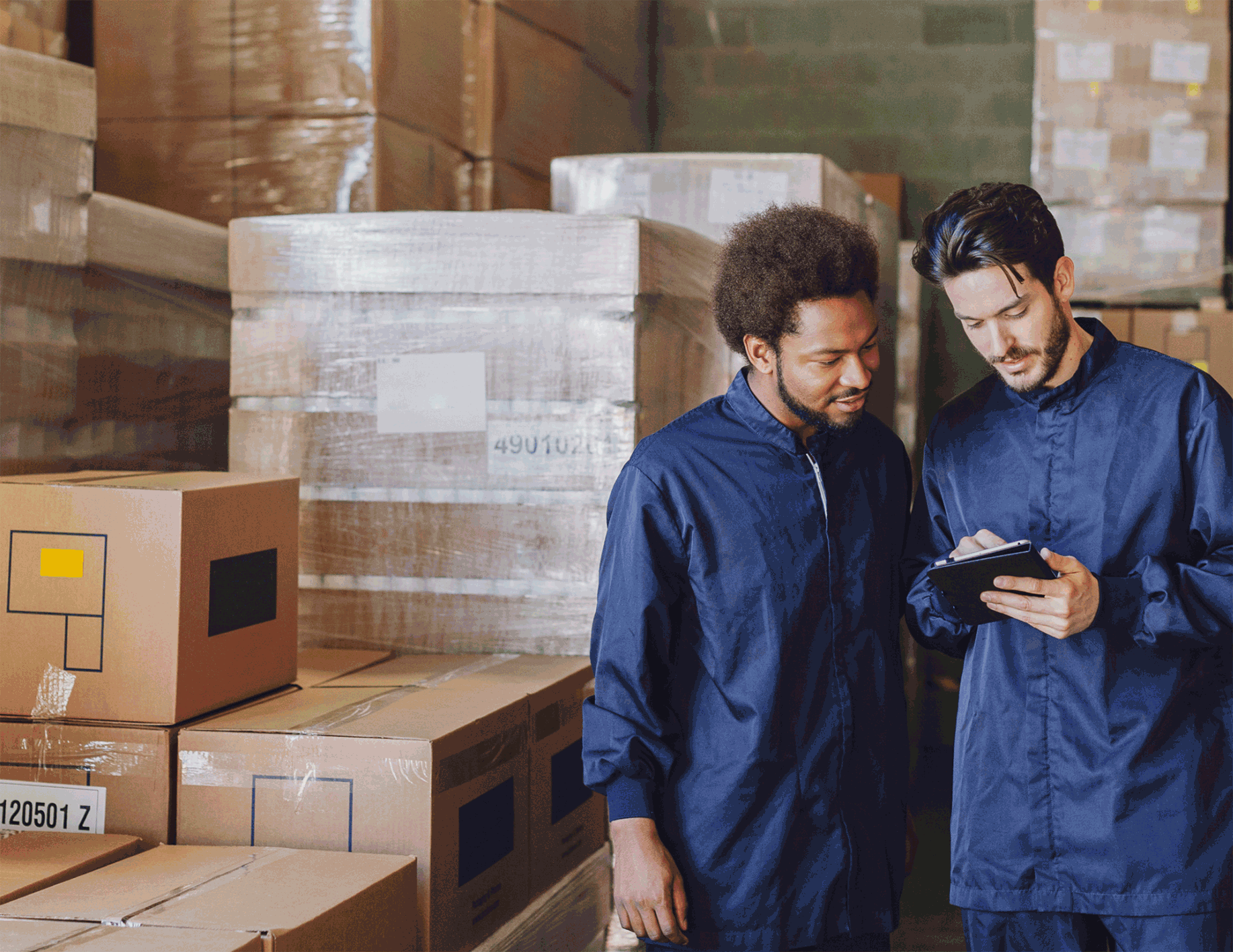 image of two individuals in a warehouse looking at ipad